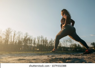 Overweight young woman stretching legs warming up before jogging outdoors. Weight losing, sports, healthy lifestyle
