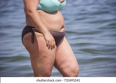 Overweight young woman in swimsuit near the sea, looking at the water, enjoys the hot sun in his summer holiday