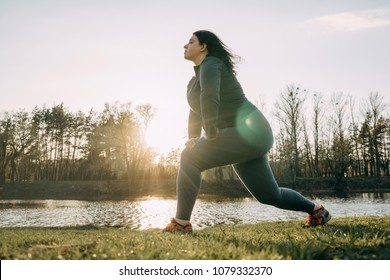 Overweight young woman warming up in morning sunlight before jogging outdoors. Weight losing, sports, healthy lifestyle