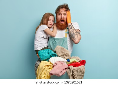 Overwhelmed depressed red haired man with thick beard, keeps hand on head, cares about small daughter, overstained with laundry and other housework, cannot understand what to do. Single father
