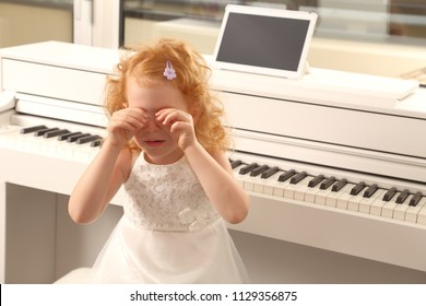 A Overwhelmed girl child crying at piano lesson
