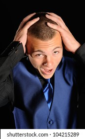 Overwhelmed Prom Date. High school student with his hands on his head as if he is overwhelmed by something.
