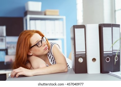 Overwhelmed red haired Caucasian woman in glasses and striped shirt slumped over at desk while looking at large work binders