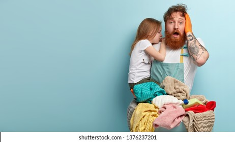 Overwhelmed surprised bearded ginger man keeps jaw dropped, keeps hand on head, carries crying daughter, feels puzzled, has to wash laundry, stands against blue studio wall with blank space.