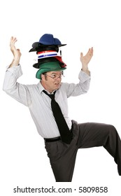 Overwhelmed white collar worker wearing too many hats and balancing on one foot.  Isolated on white.