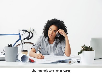 Overwork concept. Portrait of unhappy and tired young Afro American female architect working on blueprints at her workplace having bored look, holding pen in one hand and eyeglasses in other