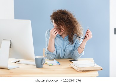 Overwork and sleep deprivation concept. Sleepy businesswoman sitting at white office desk with electronic devices, holding eyeglasses, rubbing his eyes and massaging nose bridge,has fatigue expression