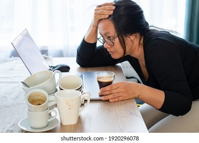 Overwork tired woman Caffeine addicted bad lifestyle concept. Young Asian woman holding cup of coffee sitting tired with many empty cups of coffee and laptop on the desk. Focus on the hand and coffee. - Shutterstock ID 1920296078