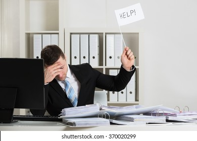 Overworked accountant holding help sign while working at desk in office