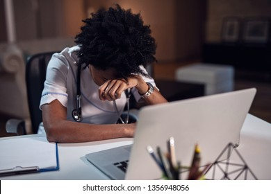 Overworked African American female doctor feeling tired after late night shift while sitting at her desk and using computer.