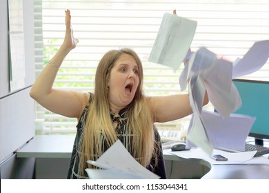 Overworked Angry businesswoman Throwing Paper All Over The Office. Stressed woman throwing charts or paperwork at office. Office worker female throws paper document pages in office.