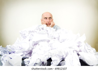 Overworked bald headed male businessman partially buried in paperwork; studio background.