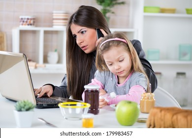 Overworked Business Woman and her little daughter in the morning. Mother read mail and make phone calls before going to work. Daughter salt breakfast.