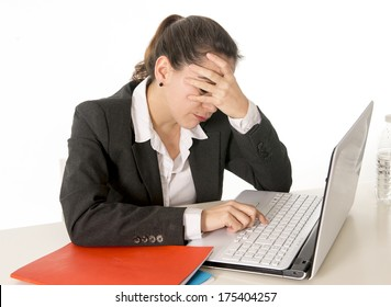 overworked business woman wearing a business suit holding her hand over her face working on her computer on a white background