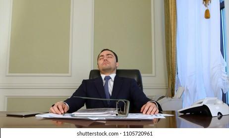 Overworked businessman falling asleep in office
