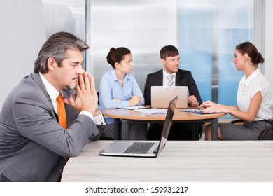 Overworked Businessman With Laptop Sitting In Front Of His Coworkers