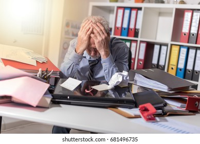 Overworked businessman sitting at a messy desk in office, light effect