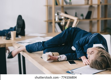 overworked businesswoman sleeping on table at messy office