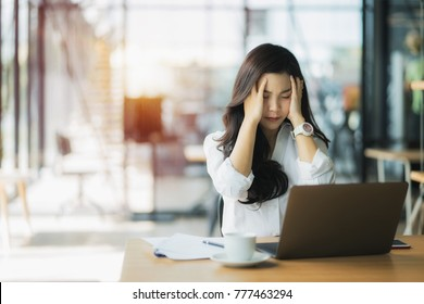 Overworked businesswoman suffering from headache and thinking how to end work.