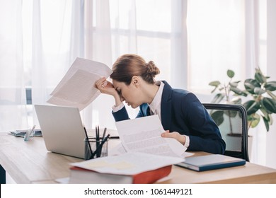 overworked businesswoman in suit with papers in hands at workplace in office