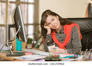 Overworked creative professional woman in her office with coffee