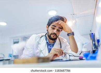 Overworked doctor in his office. Tired male scientist trying to focus, rubbing his forehead with fingers. Mid adult male doctor working long hours. Stressed male doctor sat at his desk