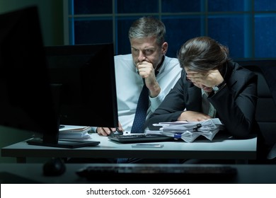Overworked employees working at night in the office