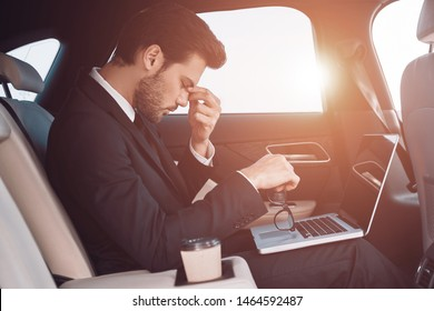 Overworked. Frustrated young man in full suit massaging nose while sitting in the car