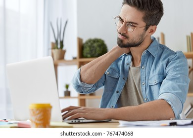 Overworked male student works all day on course paper, has pain in neck, has sedentary life, tired of sitting on one place, keyboards on laptop computer, drinks coffee. People, work, tiredness concept