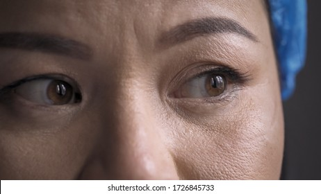 Overworked Medic feels stress after a long overtime. Super close up shot of tired doctor eyes. Woman wearing protective hat looking at side.