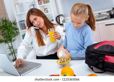 Overworked mother rushing her daughter in the morning to go faster because she late for work. She is phoning and checking documents on laptop.