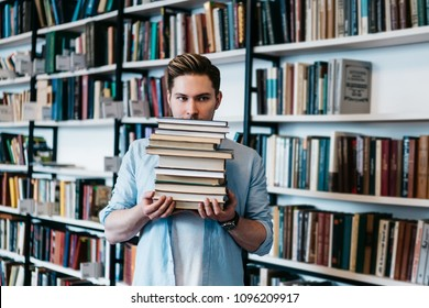 Overworked persistent young man in casual wear holding many literature books in hands for science course work.Intelligent student with textbooks standing in library interior with book shelves
