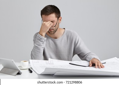 Overworked professional young male worker, has tired expression, takes off glasses as has eye pain, work all night at construction or business project, want to have sleep, tries to finish work quickly