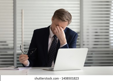 Overworked stressed middle aged business man executive take off glasses tired of computer work massage nose bridge feel headache or dry burn eye strain at workplace, sight problem bad vision concept