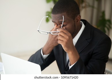 Overworked tired African American manager taking off glasses, exhausted from hardworking long hours at laptop, suffering from headache and eye strain, trying to relieve pain and stress