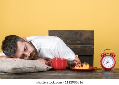 Overworked and tired bearded man sleep at breakfast table on pillow. Exhausted businessman asleep at wooden desk. Cup of tea/coffee/cappuccino, pie on plate, retro clock on table. Handsome man napping