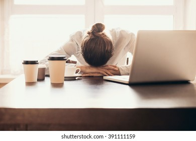 Overworked tired businesswoman sleeping on table in office. Young exhausted girl working from home. Woman using laptop. Entrepreneur, business, freelance work, student, stress, work from home concept