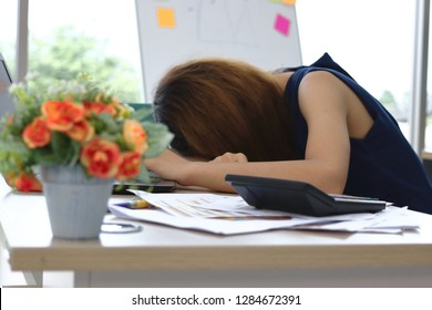 Overworked tired young Asian business woman bend down head and feeling depression in workplace of office.