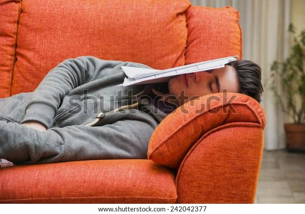 Joven cansado y sobrecargado en casa durmiendo en vez de trabajar o estudiar, descansando con la cabeza cubierta de hojas de papel