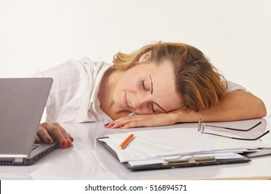 Overworked and tired young woman sleeping on des