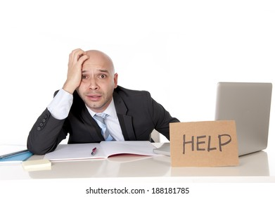 overworked unhappy and frustrated young bald latin business man in stress wearing suit and necktie sitting at office desk holding cardboard help text sign working on computer desperate and overwhelmed