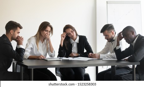 Overworked upset tired group of diverse people sitting at table, dissatisfied with work results. Frustrated female male employees feeling fatigued, worrying about paperwork documents, company crisis.