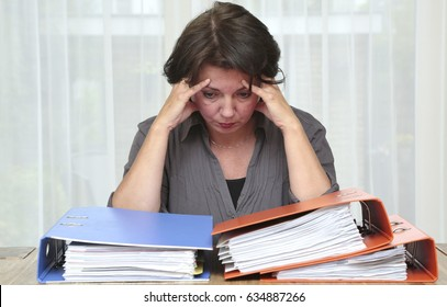 Overworked woman with a lot of paperwork on her desk