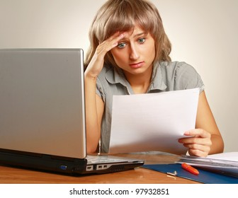 Overworked young businesswoman at her desk against grey background