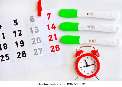 Ovulation test strip with calendar and red clock. The tests show three different results-The test is not well done.Sterile days.Positive result, It is a time for baby.Gynecology concept