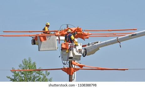 Owings,SC/USA-June 7 2018: utility linemen work on a high voltage line near Owings SC on June 7 2018. The liv lines are covered in a heavy orange insulating material to protect the workers.