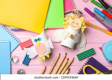 Owl and angel made of toilet paper hub among stationery on pink wooden table, flat lay