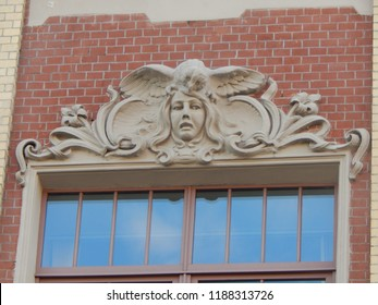 Owl bows the girl's head - architectural modeling on the house, St. Petersburg, Russia