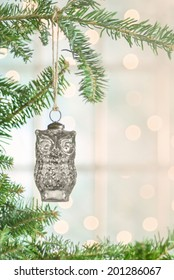 Owl Christmas ornament hung from a Christmas tree with lights and window in the background. Shot with copy space.