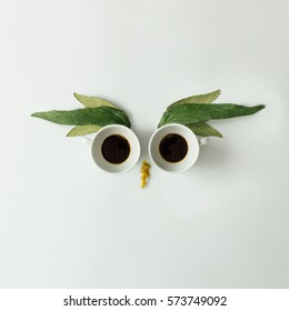 Owl face made of coffee cups and leaves. Flat lay. Coffee concept.